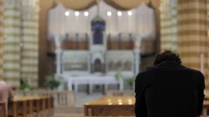 desperate man praying in a church