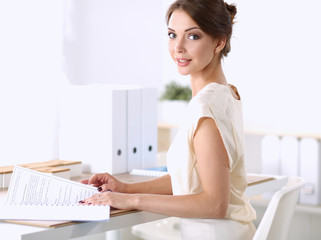 Portrait of a businesswoman sitting at  desk with  paper