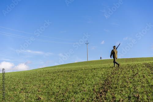 Fotobehang Jacht Gamekeeper walks over field.