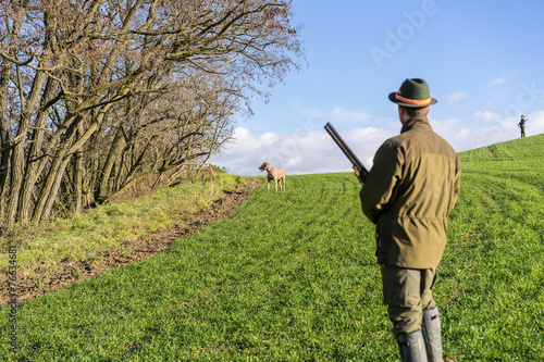 Gamekeeper giving commands to his dog. - 76634681