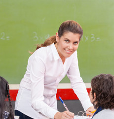 Happy female teacher checking students homework at school