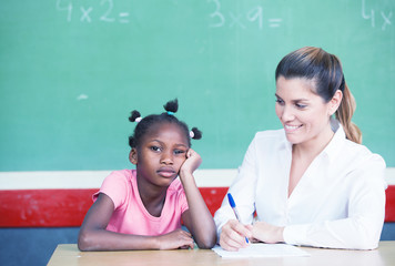 Happy female teacher comforting sad afroamerican schoolgirl