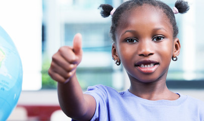 Afroamerican elementary schoolgirl with thumbs up in the classro