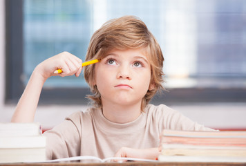 Elementary school boy at classroom desk trying to find new ideas