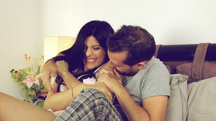 Beautiful happy couple in love in bed laughing and playing