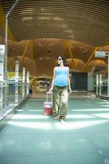 pregnant walking at airport hall