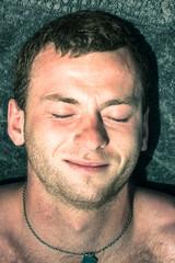 Closeup of man sleeping on towel