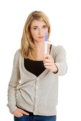 Sad young woman holding pregnancy test