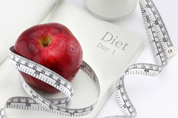 Red apple on a notebook and measuring tape, Diet concept.