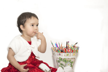 Little girl with a bucket of colored pencils