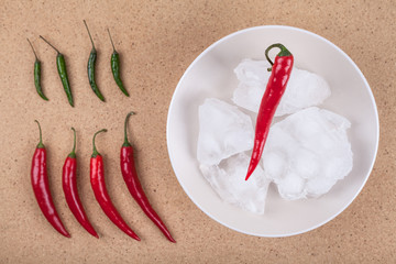 Fresh chili peppers with ice on plate