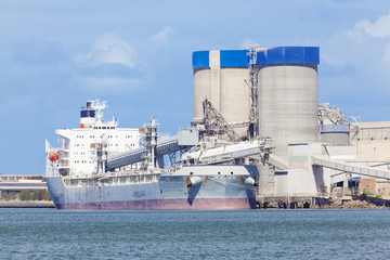 Cargo ship unloading at a cement plant