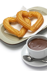 heart shape churros and hot chocolate on white background