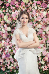 Young beautiful bride on the flowers wall background.