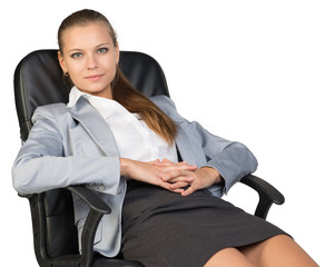 Businesswoman back in office chair, with hands clasped over her