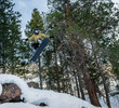 Snowboarder jumping in the forest