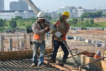 Construction Workers casting concrete using concrete hose