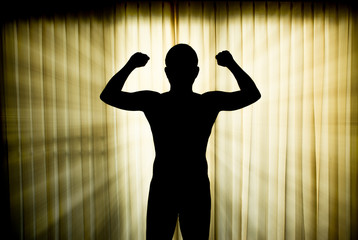 silhouette man show his muscles with lighting effect
