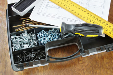 Plastic box with various screws and screwdriver