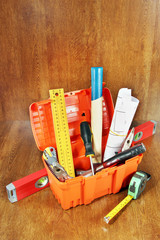 Toolbox with various working tools on a wooden table
