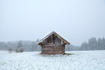 old wooden hut in snowstorm