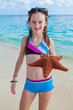 Girl enjoys summer day at the tropical beach.
