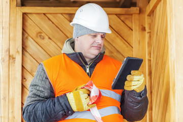 Engineer with tablet PC near wooden building