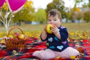Portrait of funny little girl biting an apple