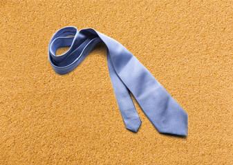 Blue necktie on sand