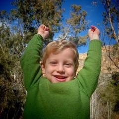 Niño rubio levantando alegre los brazos