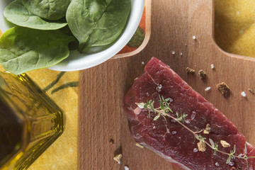 Raw beef tenderloin with spices over a wooden table
