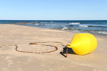Yellow buoy on the shore