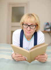 the woman wearing spectacles reads the book