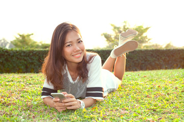 portrait of beautiful young woman lying on green grass field and