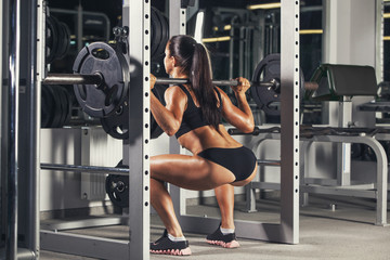 rts fitness girl with a barbell in the gym, crouches