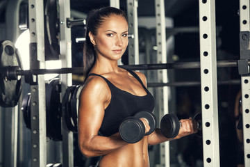 Young woman lifting the dumbbells in the gym, fitness
