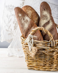 Wicker basket with different types of freshly baked bread
