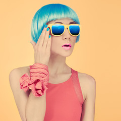 fashion lady surprise in a blue wig and sunglasses on bright yel