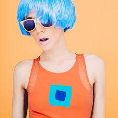 Fantastic party fashion lady in blue wig and glasses on yellow b
