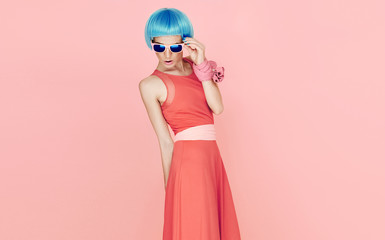 glamorous fashion lady in blue wig and sunglasses on pink backgr