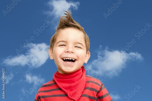 canvas print picture lachendes Kind vor blauem Himmel