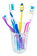 four tooth brushes and interdental brush in glass