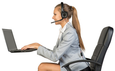 Businesswoman in headset, typing on laptop keyboard