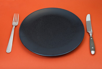 empty black plate with fork and knife on red