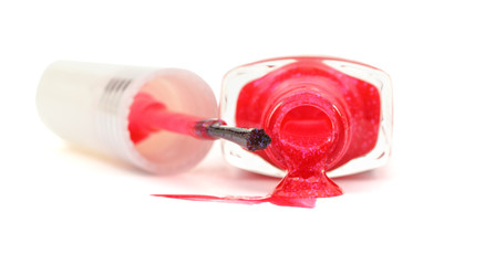 bottle with spilled pink nail polish on white