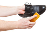 Shoeshiner cleaning black shoes by brush poster