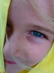 Ojo azul de niña rubia con toalla amarilla