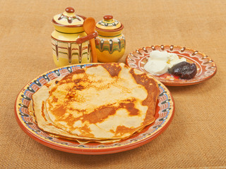 Fried pancakes on pottery with jam and cream village