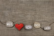 canvas print picture - One red heart with stones on wooden background.