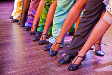 dancer legs on stage in dance position, male female colorful